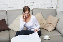 Frau, die zu Hause am Telefon spricht Lizenzfreie Stockbilder