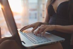 Frau, die zu Hause unter Verwendung des Laptops, arbeitend mit Computer sitzt Lizenzfreies Stockbild