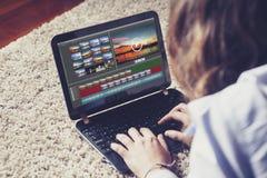 Frau, die zu Hause Video mit einem Laptop redigiert Stockbild