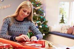 Frau, die zu Hause Weihnachtsgeschenke einwickelt Lizenzfreies Stockfoto