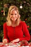 Frau, die zu Hause Weihnachtskarten bildet Lizenzfreies Stockbild