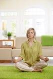 Frau, die zu Hause Yogameditation tut Lizenzfreies Stockfoto