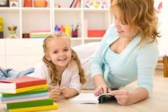 Frau, die zu ihrem kleinen Mädchen liest Lizenzfreie Stockbilder