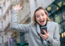 Frau, die zu ihrem Telefon auf der Straße, im Freien schaut stockfotografie