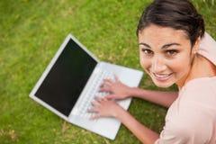 Frau, die zu ihrer Seite bei der Anwendung eines Laptops schaut Stockfoto
