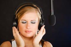 Frau, die zu tragenden Kopfhörern des Mikrofons im Studio singt Lizenzfreies Stockbild