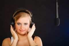 Frau, die zu tragenden Kopfhörern des Mikrofons im Studio singt Lizenzfreies Stockfoto
