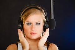 Frau, die zu tragenden Kopfhörern des Mikrofons im Studio singt Lizenzfreie Stockbilder