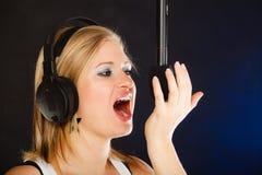 Frau, die zu tragenden Kopfhörern des Mikrofons im Studio singt Lizenzfreie Stockfotografie
