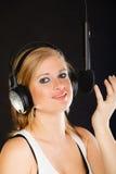 Frau, die zu tragenden Kopfhörern des Mikrofons im Studio singt Stockbilder