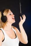 Frau, die zu tragenden Kopfhörern des Mikrofons im Studio singt Stockbild