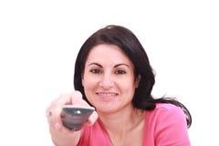 Frau, die zuhause Gernsehkanäle ändert Stockbild