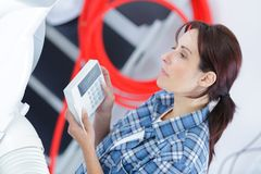 Frau, die zuhause Knopf auf Sicherheitssystem bedrängt lizenzfreies stockfoto