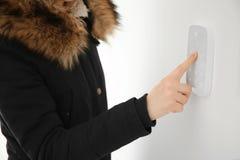Frau, die zuhause Sicherheitssystem verwendet stockfotografie