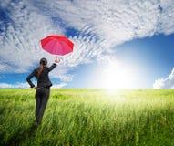 Frau, die zum blauen Himmel mit rotem Regenschirm steht Lizenzfreie Stockfotos