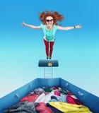 Frau, die zum Haufen von Kleidung fliegt Stockfotografie