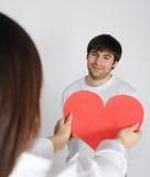 Frau, die zum Liebessymbol des jungen Mannes gibt Lizenzfreies Stockbild