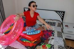 Frau, die zum Reisen fertig wird junge Frau, roter Koffer, Sitzen, wartend, Sommerferien, bunt und reisen um Welt Stockfotos