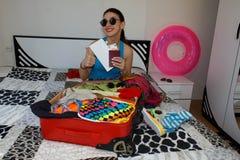 Frau, die zum Reisen fertig wird junge Schönheit, roter Koffer, Sitzen, wartend, Sommerferien, buntes, reisendes AR Stockfotografie