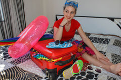 Frau, die zum Reisen fertig wird junge Schönheit, roter Koffer, Sitzen, wartend, Sommerferien, buntes, reisendes AR Stockfotos