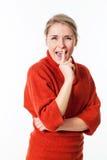 Frau, die zum Spaß mit Index auf Lippengeheimnis lacht Lizenzfreie Stockfotos