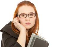 Frau, die zum Telefon benennt und ein schwarzes Faltblatt anhält Lizenzfreie Stockfotos