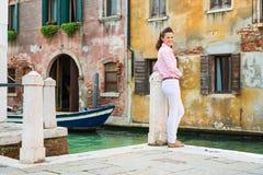 Frau, die zurück über der lächelnden Schulter, stehender naher Kanal schaut Lizenzfreie Stockfotografie