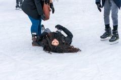 Frau, die zurück auf ihr auf dem Eis beim Eislauf an einer allgemeinen Eislaufeisbahn liegt Stockfoto