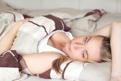 Frau, die zurück auf ihrem träumenden Bett liegt Lizenzfreie Stockfotografie
