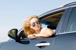 Frau, die zurück vom Autofenster schaut Lizenzfreies Stockbild