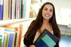 Frau, die zwei Bücher in der Bibliothek hält Lizenzfreie Stockfotografie