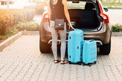Frau, die zwei blaue Plastikkoffer zum Autokofferraum lädt stockfotos