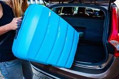 Frau, die zwei blaue Plastikkoffer zum Autokofferraum lädt stockfotografie