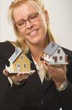 Frau, die zwei Häuser anhält Stockfotos