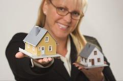Frau, die zwei Häuser anhält Stockfoto