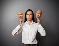 Frau, die zwei Masken mit unterschiedlicher Stimmung hält Lizenzfreies Stockfoto