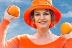 Frau, die zwei Orangen hält Lizenzfreie Stockfotos