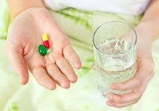 Frau, die zwei Pillen und ein Glas Wasser anhält. Lizenzfreie Stockfotografie