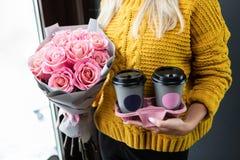 Frau, die zwei Tasse Kaffees hält, um zu gehen und einen Blumenstrauß lizenzfreie stockfotografie