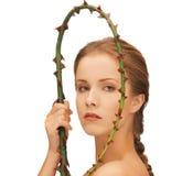 Frau, die Zweig mit den Dornen anhält Lizenzfreies Stockfoto