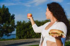 Frau, die zwischen einem Hamburger und einem Apfel wählt Lizenzfreies Stockbild