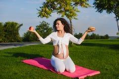 Frau, die zwischen einem Hamburger und einem Apfel wählt Stockbilder