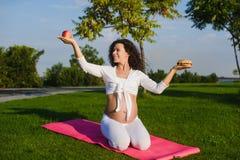 Frau, die zwischen einem Hamburger und einem Apfel wählt Lizenzfreie Stockbilder