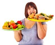Frau, die zwischen Frucht und Hamburger wählt. Lizenzfreies Stockbild