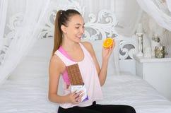 Frau, die zwischen Fruchtbonbons wählt lizenzfreies stockfoto