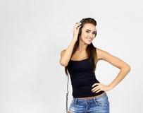 Frau DJ mit Kopfhörern in den Jeans und im schwarzen Hemd Stockbild
