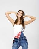 Frau DJ mit Kopfhörern in den Jeans und im weißen Hemd Stockfotografie
