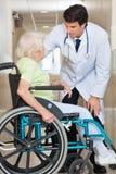 Frau Doktor-Communicating With Senior, die herein sitzt stockfotos