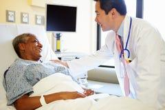 Frau Doktor-Talking To Senior im Krankenhauszimmer lizenzfreies stockfoto