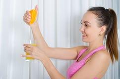 Frau drückt Orangensaft zusammen Lizenzfreies Stockbild